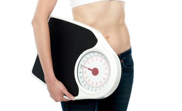 Closeup shot, woman carrying weighing machine
